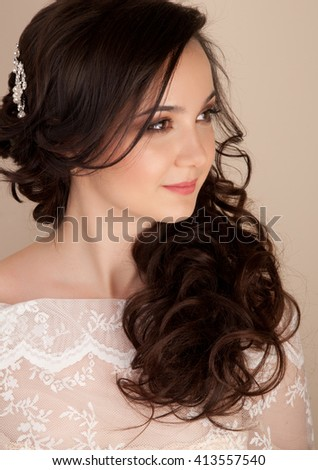 Portrait of beautiful bride with curly hairstyle and sexy makeup in lace dress - stock photo