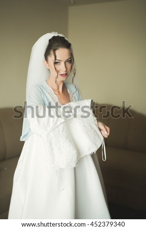 Portrait of beautiful bride with fashion veil at wedding morning.