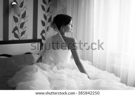 Portrait of beautiful bride with fashion veil posing at home at wedding morning. Makeup. Blondegirl with elegant hair styling. Wedding dress. - stock photo