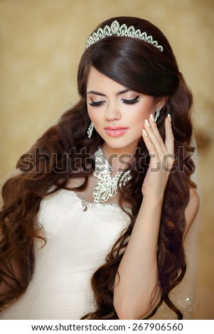 Portrait of beautiful brunette bride with long wavy hair styling and Makeup. Wedding dress. Diamond expensive jewelry decoration. - stock photo