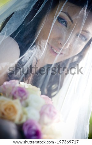 Portrait of beautiful brunette bride with veil and bouquet