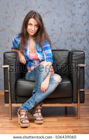 Portrait of beautiful brunette girl in a plaid shirt, sitting in leather chair against the wall with a retro pattern - stock photo