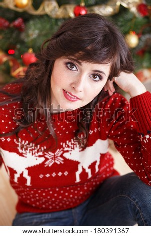 Portrait of beautiful brunette girl in a red sweater with a deer near the Christmas tree