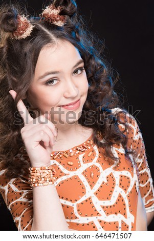 Portrait of beautiful brunette girl in orange dance costume for stage performance