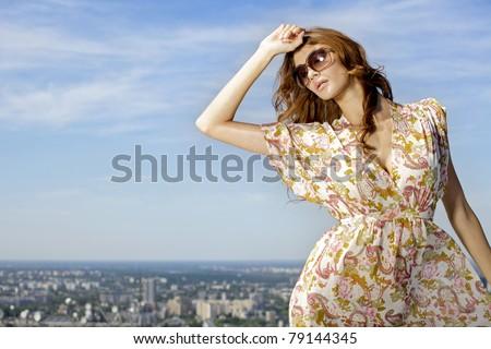 portrait of beautiful brunette girl in sunglasses on background blue sky - stock photo