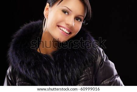 portrait of beautiful brunette girl in winter clothes on black - stock photo