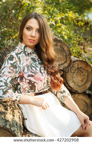 Portrait of beautiful brunette girl poses on nature background outdoors - stock photo