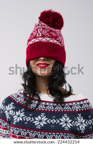 Portrait of beautiful brunette girl with knitted beanie on her face. Christmas mood - stock photo