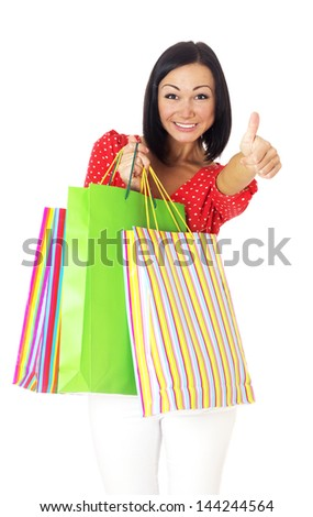 Portrait of beautiful brunette girl with paper bags going shopping and showing ok sign, isolated on white background. - stock photo