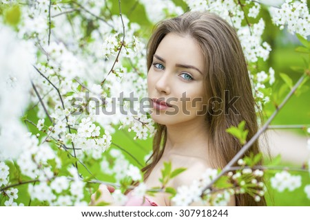 Portrait of beautiful brunette in spring blossom  - stock photo