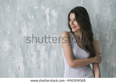 Portrait of beautiful brunette looking away while smiling and embracing herself with one arm - stock photo