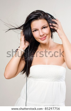 Portrait of beautiful brunette music lover with windblown hair.