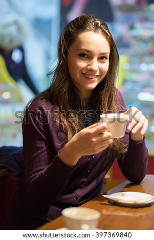 Portrait of beautiful brunette posing with a cup