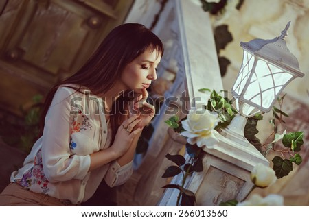 Portrait of beautiful brunette sensual eyes in profile, in the interiors of the house, in beige. In the background is a ladder and a flashlight - stock photo