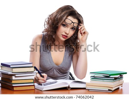 portrait of beautiful brunette student girl in glasses sitting among the books and writing in blocknote