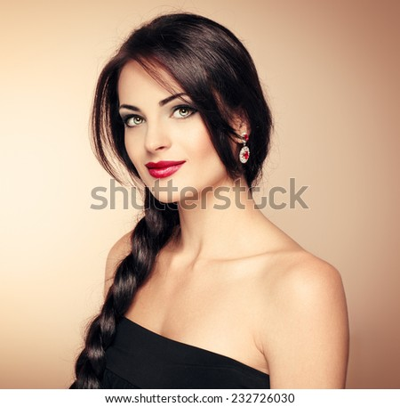 Portrait of beautiful brunette vogue model evening dressed with fashionable hairstyle and professional makeup. Young pretty Caucasian woman with long hair and naked shoulders posing in studio.  - stock photo