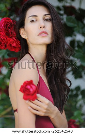 Portrait of beautiful brunette woman beside a wall from rosebush - stock photo