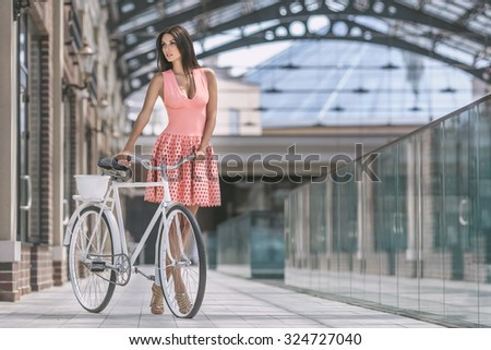 portrait of beautiful brunette woman in pink dress with bicycle - stock photo