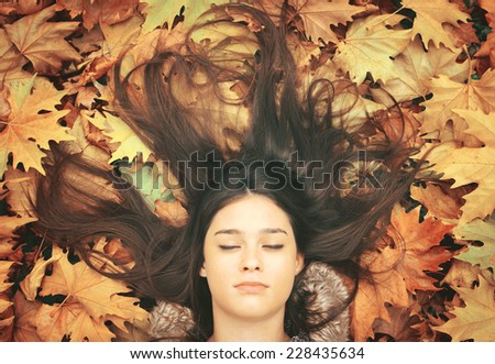 Portrait of beautiful brunette woman lying on maple leaves - stock photo