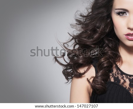 Portrait of beautiful brunette woman over grey background