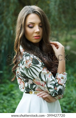 Portrait of beautiful brunette woman poses on green background outdoors - stock photo