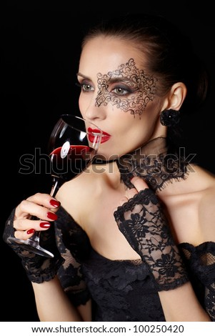 portrait of beautiful brunette woman sommelier in lacy black dress and gloves with face body art holding glass of red wine in hand