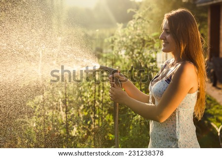 Portrait of beautiful brunette woman watering garden bed with vegetables - stock photo