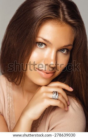 Portrait of Beautiful Brunette Woman with Jewelry Ring. Long Hair and Clean Skin. Close Up