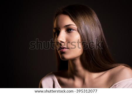 Portrait of beautiful brunette woman with natural look and without makeup on black background
