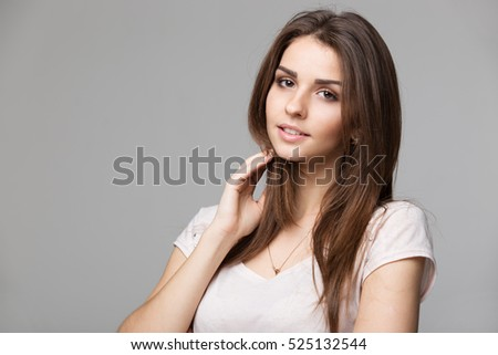 Portrait of beautiful brunette woman with natural make-up, on grey background