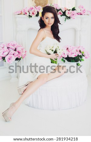 Portrait of Beautiful Brunette Woman with Perfect Fashion Makeup and Hairstyle. Fashion Girl sitting on Arm-chair at Interior with Peony. Vintage Toning - stock photo