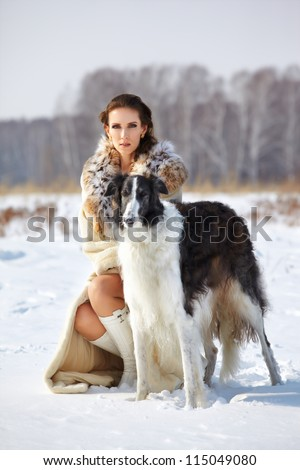 portrait of beautiful brunette woman with russian wolfhound in fur coat in snowy filed with winter forest on background