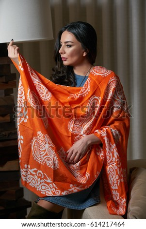 Portrait of Beautiful brunette, young oriental beauty female model with black long hair, Dressed in a denim dress clothing with Oriental orange scarf and oriental jewelry.
