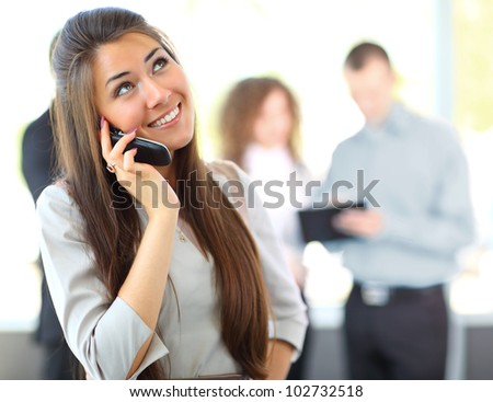 Portrait of beautiful business woman on the phone at modern building