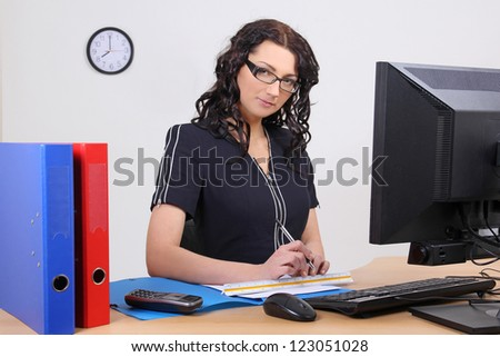 portrait of beautiful business woman sitting at her workplace - stock photo