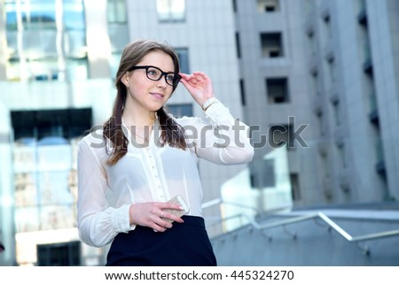 Portrait of beautiful business woman wearing glasses and hold smart phone. Looking to the side. - stock photo