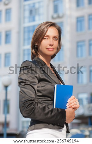 Portrait of beautiful business woman with diary - stock photo