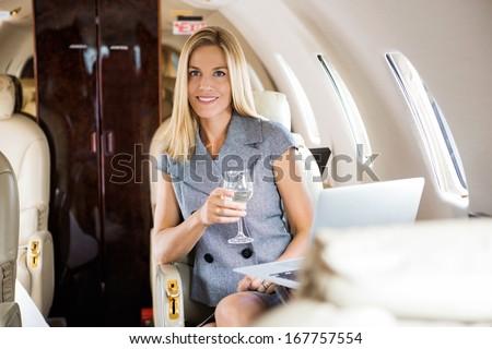 Portrait of beautiful businesswoman having wine in corporate jet - stock photo