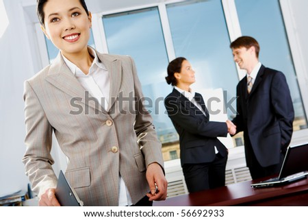 Portrait of beautiful businesswoman in suit on background of handshaking partners