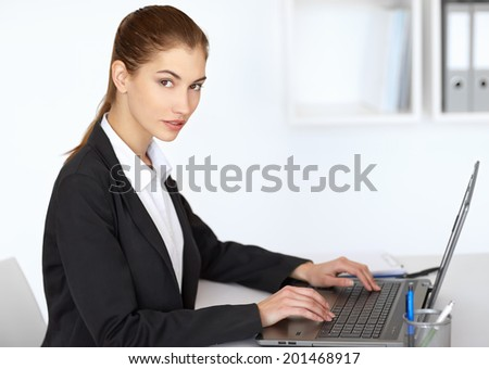 Portrait of beautiful businesswoman sitting at table in office and working at laptop