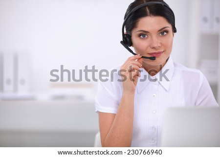Portrait of beautiful businesswoman working at her desk with headset and laptop - stock photo