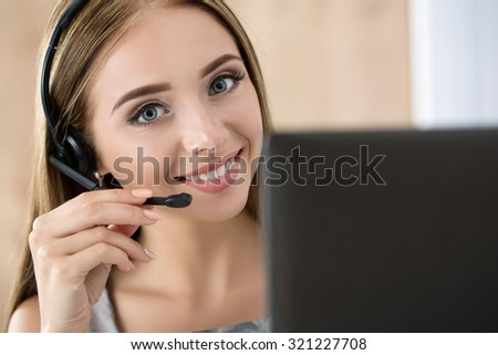 Portrait of beautiful call center operator at work. Woman with headset talking to someone online - stock photo