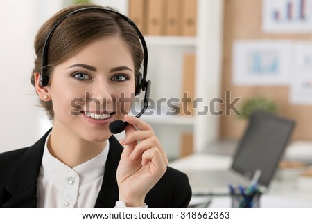 Portrait of beautiful call center operator at work. Woman with headset talking to someone online