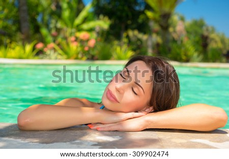 Portrait of beautiful calm woman with closed eyes relaxing in the pool, spending summer vacation on luxury spa resort - stock photo