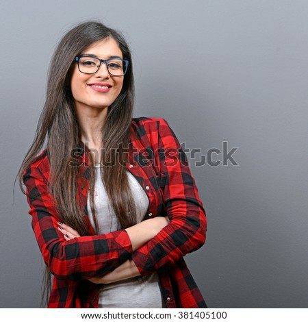 Portrait of beautiful casual woman against gray background - stock photo
