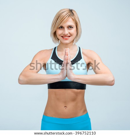 Portrait of beautiful caucasian blonde sporty woman. Young athlete holding hands in yoga style, smiling and looking at camera - stock photo