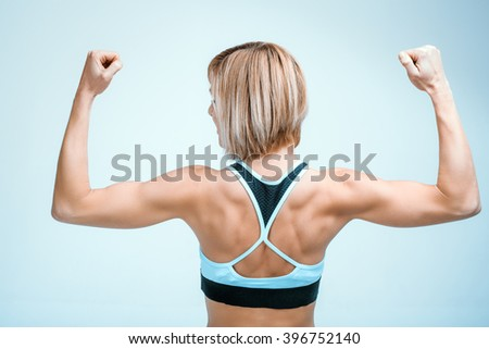 Portrait of beautiful caucasian blonde sporty woman. Young athlete showing strong arms and back - stock photo