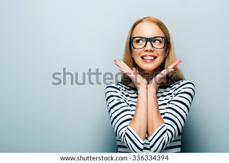 Portrait of beautiful caucasian blonde woman standing on grey background. Young woman with glasses cheerfully smiling and looking aside - stock photo