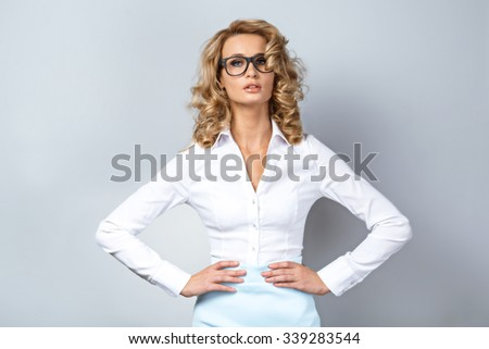 Portrait of beautiful caucasian blonde woman with curly hair standing on grey background. Young business woman with glasses looking at camera - stock photo