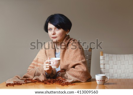 Portrait of beautiful Caucasian brunette mid age woman covered with blanket sitting at table drinking tea coffee holding cup in hands looking in camera, waiting for somebody, end of day, evening night - stock photo